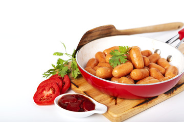 Fried sausages in the red pan and fresh tomato, ketchup, coriander on the wood plate, isolated white background.