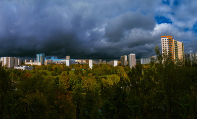 Panorama residential disctrict of Moscow at autumn with dark beautiful rainy clouds in the blue sky, soviet buildings, a large park – panoramic view of the city in high resolution