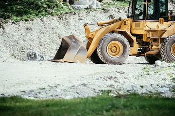 Bagger auf Baustelle, Schottergrube und Bäume im Hintergrund