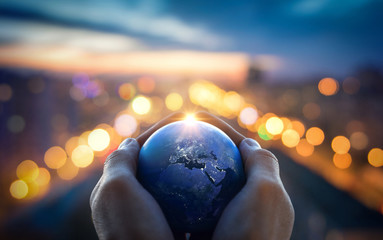 The globe Earth in the hands of man against the night city. Concept on business, politics, ecology and media. Elements of this image furnished by NASA