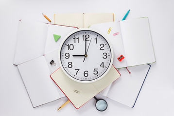school accessories and wall clock at notebook