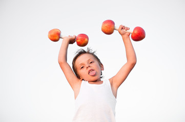 strong healthy cute kid in white shirt lifting dumbbells made from fresh apples