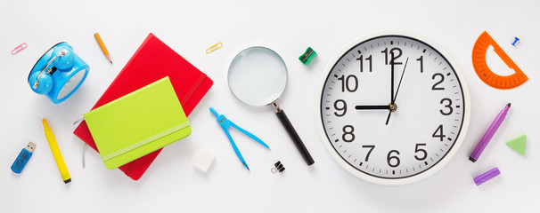 school accessories and wall clock at white background