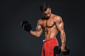 Young handsome athlete bodybuilder, in beautiful sportswear, demonstrates abdominals, against a dark background. Concept - power, beauty, biceps, triceps, sports equipment, gym, sports nutrition.