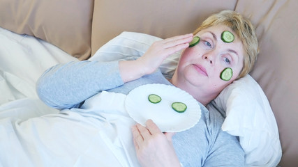 woman makes face mask with sliced cucumbers in bed
