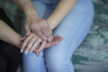 Hands of an elderly woman holding the hand of a younger woman.