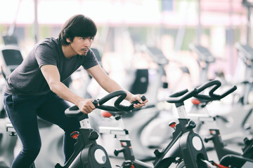 Footage of a man working out in gym on the exercise bike, young man cycling in the gym. man exercising in fitness gym for good health.