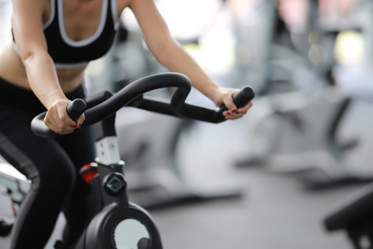 Close-up footage of a women working out in gym on the exercise bike, young woman cycling in the gym. female exercising in fitness gym for good health.