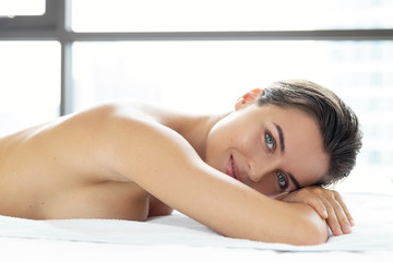 Young and beautiful woman is lying and relaxing after massage