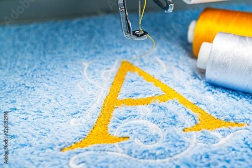 Alphabet logo design on towel in hoop of embroidery machine