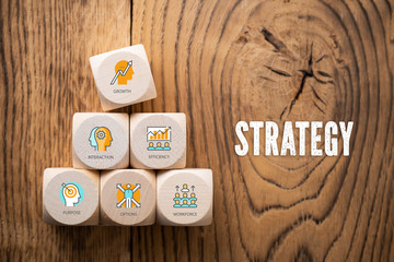"""Cubes with symbols and the word """"strategy"""" on wooden background"""