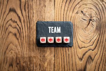 """Schiefertafel mit Wort """"TEAM"""" und Würfel mit Team-Symbolen"""