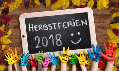"""in bunten Farben angemalte Kinderhände vor herbstlich dekorierter Kreidetafel und der Aufschrift """"Herbstferien 2018 :)"""""""