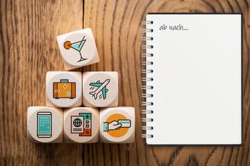 """Reisesymbole auf Würfeln und Notizblock mit Aufschrift """"ab nach..."""" auf Holzuntergrund"""