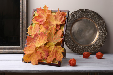 Picture frame  with maple leaves composition as autumn decoration in interior. Handmade colorful autumn fall composition in frame and dried plants chinese lantern on wooden shelf.
