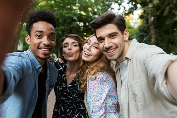 Young group of friends outdoors in park having fun take a selfie by camera.