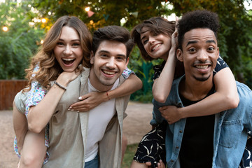 Group of young friends party outdoors in park having fun.