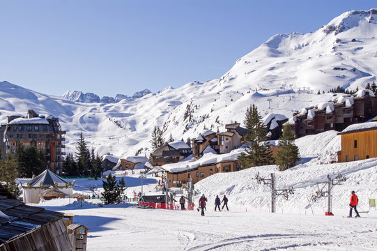 Avoriaz, part of Portes du Soleil ski area, high altitude ski resort in the French Alps. Picture taken in centre of the resort with thick snow covering the chalets and hotel rooftops and people walkin
