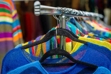 Colorful clothes hang on shelf in a market