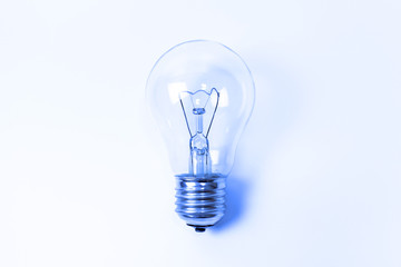 Blue toned incandescent lamp buld on light blue background with copy space