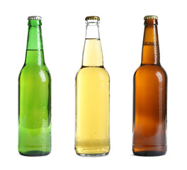Set with different cold beer bottles on white background