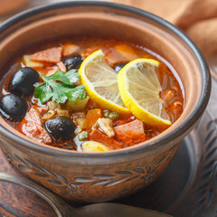 Traditional Russian soup Solyanka with meat, sausages, vegetables, capers, pickles and olives with lemon, seasonings and spices. Served with sour cream. Rustic style