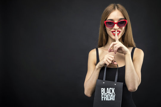 Sexy woman wears red sunglasses holding sale shopping bag before isolated dark background, black friday concept