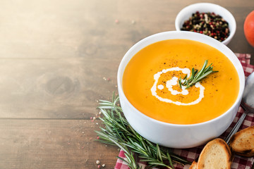 Pumpkin Cream soup on wooden  background. Autumn yellow cream-soup in country style. Top view.