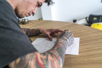 Young man tattooed drawing a tattoo