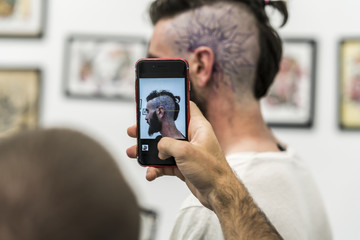 Portrait with the cell phone to the drawing of the tattoo on the head.