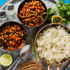 vegan curry with green peas and basmati rice served on a blue table tray, healthy Indian comfort food