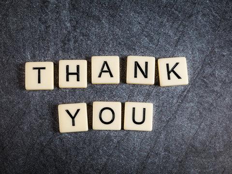 Letter tiles on black slate background spelling Thank You