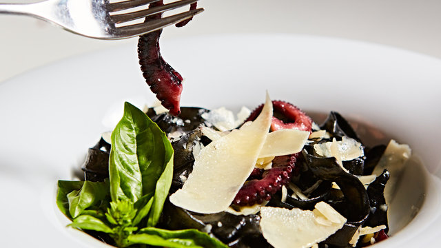 Pasta with black cuttlefish ink, octopuses and parmesan.