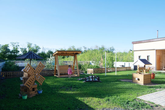 Beautiful backyard of a country house. Happy lifestyle concept. There are swing, sandpit for children, flowers, scenery, mill, bridge, garden