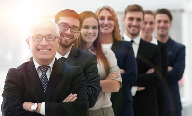 senior businessman standing in front of his business team