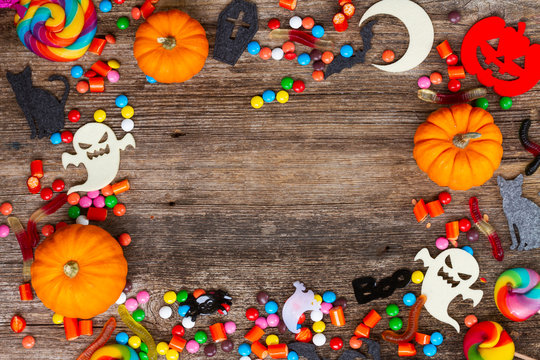 Trick and treat - colorful halloween flat lay frame on aged wood with copy space on wooden background