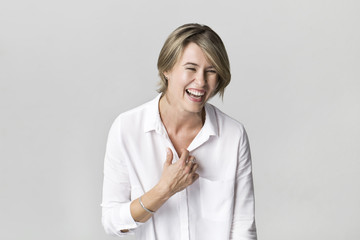 Happy young blonde woman wearing white shirt smiling portrait against white background