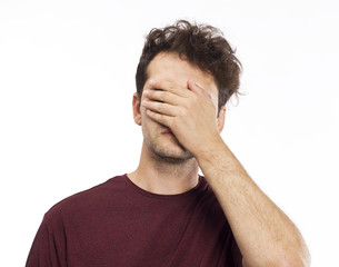 Young man blocking face with hands