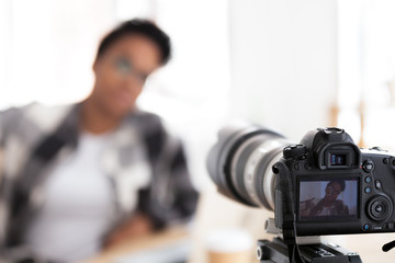 Closeup camera young attractive black american woman blogger sitting indoors at home recording her daily video blog vlog, model passing casting. Serious concentrated, confident girl looking at camera