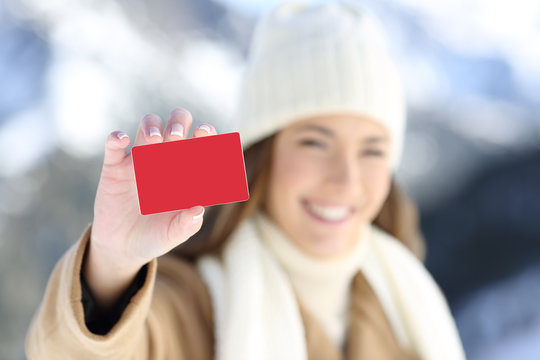 Woman showing a blank credit card in winter