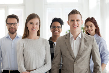 Group young millennial multiracial students business people professionals company staff standing together looking at camera. Five attractive smiling workers in office. Successful diverse team concept