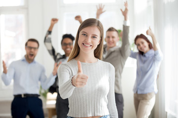 Attractive happy woman with group of multiracial millennial businesspeople on background standing smiling together in office with thumbs up looking at camera. Teamwork, collaboration approval concept