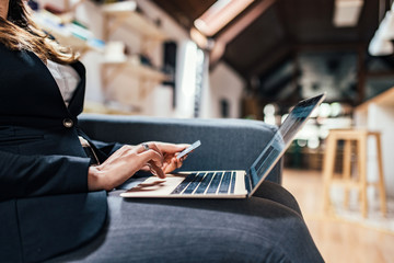 Close-up image of female person using laptop and credit card for online shopping.
