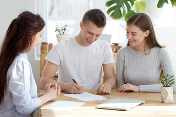 Three young millennial people sitting at the desk in office agency. Married family couple happy smiling sign a contract paper document. Relocate move a new home, buying real estate property concept