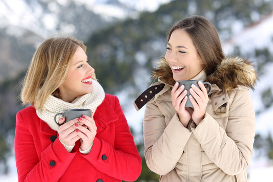 Two women talking with coffee cups in winter