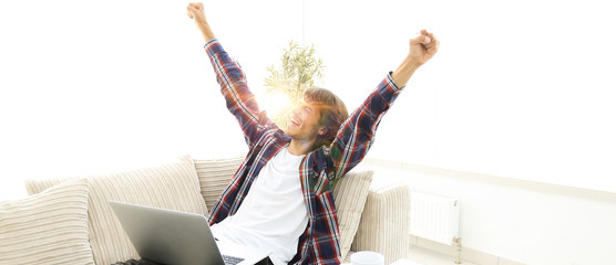 happy young man looking at laptop screen