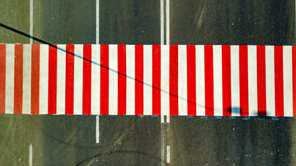 a new red and white colored pedestrian crossing is located on the highway. Aerial view