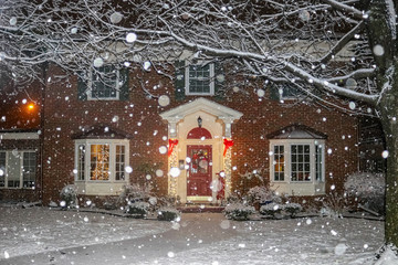 Snowfall on beautiful brick house with columns and bay windows with Christmas tree light up and red sled and wreath on porch
