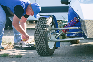 The mechanic serves the car. All-wheel drive off-road racing buggy car