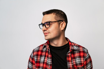 portrait in profile of a young man in a red plaid shirt and in stylish eyeglasses with black rim on a white background in the studio